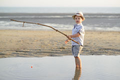 Child is fishing on the beach at the seaside Royalty Free Stock Photography