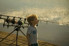 Child is fishing. Boy stand on fishing pier royalty free stock photography