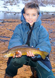 Child fishing - holding a large trout. Boy fishing in the winter, smiling and holding a big sized Brown Trout and his fly rod (or pole) and reel royalty free stock image
