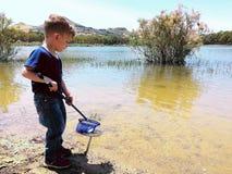 Child fishing. On the shore of pozzillo lake, Sicily Royalty Free Stock Photo