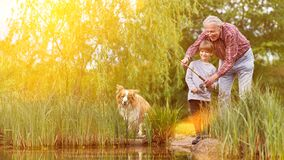 Free Child Fishing With Grandpa And Dog By The Lake In Summer Royalty Free Stock Photos - 188846798