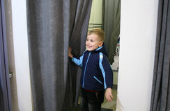 Child in fitting-room. With small coat Royalty Free Stock Photography