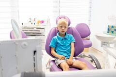 A child a five year old boy in a blue t shirt is sitting in a lilac chair in a white office
