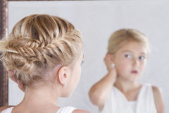 Child fixing her hair while looking in the mirror. Stock Image