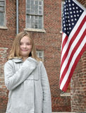 Child and flag. One young cute child with hand on her heart near an American Flag outdoors Royalty Free Stock Photography