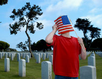 Child with flag in cemetery. Young girl covering face with American flag in military cemetery with graves receding into distance Royalty Free Stock Image