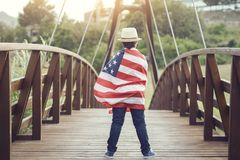 Child with the flag of the United States. On wooden bridge royalty free stock photos