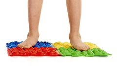Child flatfoot treatment. Using special massage carpet royalty free stock images