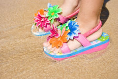 Child Flip Flops. Feet of a two years old child girl on the sand, wearing a pair of a lovely flower decorated flip flops. Beach, summer, fun, vacation concept stock photography
