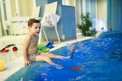 Child sitting on edge of pool stock images