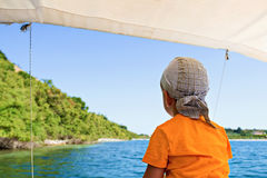 Child floats on a catamaran on the picturesque Lake Stock Photography