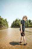 Child on flooded road Stock Image