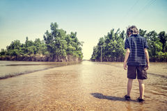Child on flooded road. Child standing on flooded road in rural America after a springtime flood with vintage filtered effect Stock Photos