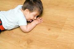 Child on floor. Baby boy child lying on hardwood floor Stock Photos