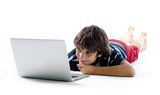 Child on the floor using laptop computer Stock Images