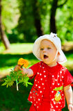 Child with flower. The girl holds out a flower in your hand Royalty Free Stock Photos