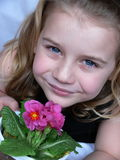 Child with flower. Child with little ping primroses royalty free stock photo