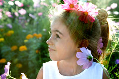 Child with flower in hair. Side portrait of smiling young girl with colorful flowers in hair, nature background Royalty Free Stock Photo