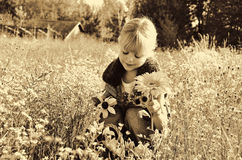 Child with flowers in sepia. Little girl with autumn flowers in sepia tones Stock Photography