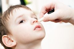 Child with flu and drops in the nose Stock Image