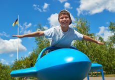 Child fly on blue airplane attraction in park, happy childhood, summer vacation concept Royalty Free Stock Photo