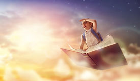 Child flying on the book. Back to school! Happy cute industrious child flying on the book on background of sunset sky. Concept of education and reading. The Royalty Free Stock Photos