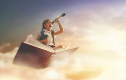 Child flying on the book. Back to school! Happy cute industrious child flying on the book on background of sunset sky. Concept of education and reading. The Royalty Free Stock Photography