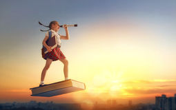Child flying on the book. Back to school! Happy cute industrious child flying on the book on background of sunset urban landscape. Concept of education and Stock Photos
