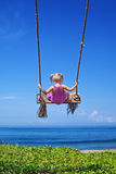 Child on flying high on rope swing on sea beach Royalty Free Stock Photos