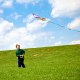 Child flying kite and playing outdoors Stock Image