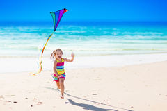 Child flying kite on tropical beach Royalty Free Stock Photos