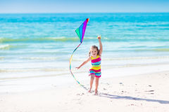 Child flying kite on tropical beach Stock Photos