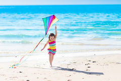 Child flying kite on tropical beach Stock Photo