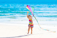 Child flying kite on tropical beach Stock Photography