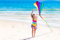 Child flying kite on tropical beach. Happy laughing little girl flying a colorful kite running and jumping in sand on beautiful tropical beach during active Stock Photography