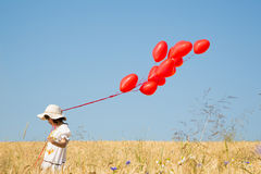 Child with flying red heart balloons on the blue sky background. Stock Photo