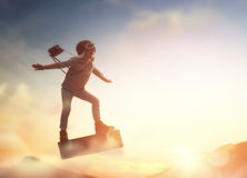 Child flying on a suitcase. Dreams of travel! Child flying on a suitcase against the backdrop of sunset Royalty Free Stock Images