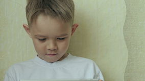 Child focused on screen tablet. stock video