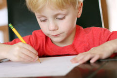 Child Focusing on Work as he Writes with Pencil Stock Photo