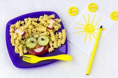 Child food. Funny food. Plate with pasta. With vegetables in the form of funny face . Children`s menu. Children`s lunch concept stock photos