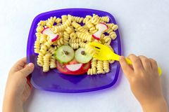 Child food. Funny food. Plate with pasta. With vegetables in the form of funny face. Children`s menu. Children`s lunch concept. Children`s hands hold the fork stock image