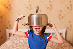 Child fool around with pan and serving spoon. stock photos