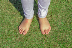 Child foot on the green grass Stock Photos