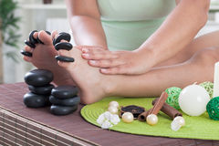 Child foot ready to spa treatment with massage stones. Boy foot ready to spa treatment with massage stones Royalty Free Stock Photos