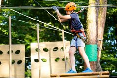 Child in forest adventure park. Kid in orange helmet and blue t shirt climbs on high rope trail. Agility skills royalty free stock images