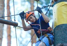 Child in forest adventure park. Kid in orange helmet and blue t shirt climbs on high rope trail. Agility skills and climbing stock photos