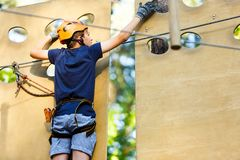 Child in forest adventure park. Kid in orange helmet and blue t shirt climbs on high rope trail. Agility skills stock image