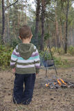 The child in the forest stands near the fire where the food is c Royalty Free Stock Photos