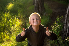 Child in forest, thumbs up Royalty Free Stock Images