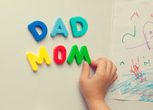 Child forms mom dad words on refrigerator. Closeup photograph of child hand forming mom and dad words with magnetic letters on refrigerator door stock photos
